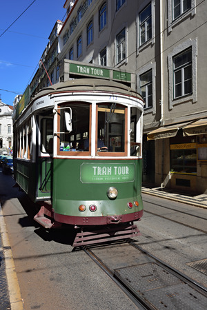 wood railways: LISBON, PORTUGAL - June 11, 2017: Vintage green tram shown on a street. Old trams is one of the main symbols of capital of Portugal