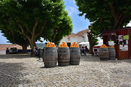 portugal agriculture: Obidos, Portugal - June 1, 2017: Heap of bright ripe oranges at the barrels on the small square of the medieval city of Obidos, Portugal