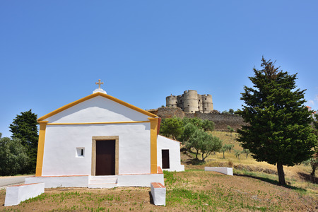 Beautiful view on the small white chapel and the Castle of Evoramonte on background. Initiated around 1306 it was enlarged in the later centuries in the Manueline style.