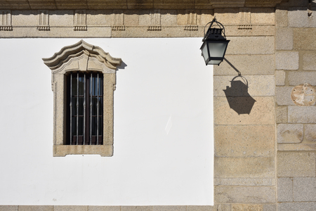plastered wall: Window and street lamp on the white stone wall of medieval house in Evora, Portugal