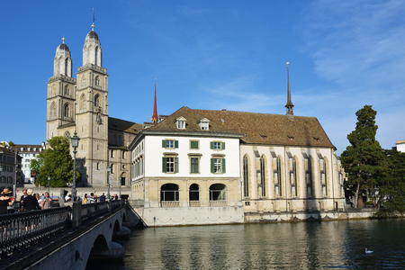 pedestrian bridges: Zurich, Switzerland - June 14, 2017: View on the Muensterbruecke bridge over the Limmat river and the Grossmunster cathedral in the city of Zurich, the capital of the Swiss canton of Zurich