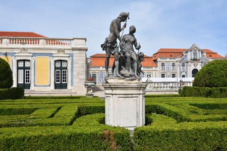 Queluz, Portugal - June 3, 2017: Neptune gardens, sculpture Meleager and Atlanta  by sculptor John Cheere  and the facades of the Queluz Royal Palace Editorial
