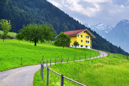Beautiful view of idyllic mountain scenery in the Alps with traditional chalet with green alpine meadows and snow covered mountain peak in Uri canton nearby Altdorf, Switzerland Stock Photo