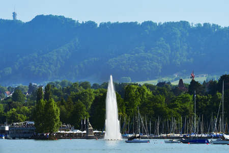 Zurich, Switzerland - June 14, 2017: Beautiful view of the fountain at Mythenquai in the Zurich lake and the cityscape of Zurich old town at sunset Switzerland Editorial