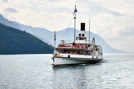 Lucerne, Switzerland - June 14, 2017: Vintage Swiss paddle wheel steamer carrying many passengers on lake Lucerne. By fog covered Alps mountains peaks on background. Switzerland
