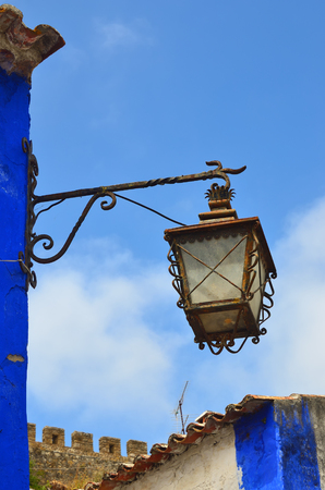 plastered wall: Ancient streetlight on background of the blue sky, Obidos, Portugal