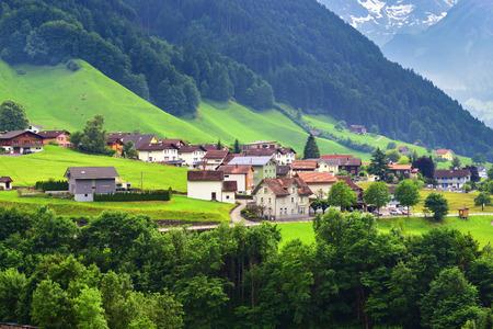 Splendida vista del paesaggio di montagna idilliaca nelle Alpi con chalet tradizionali nei prati alpini verdi del villaggio n nel canton Uri nelle vicinanze città di Altdorf, Svizzera