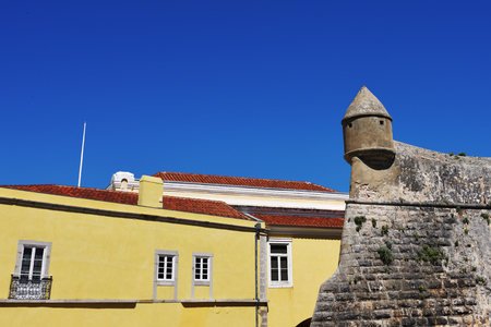 plastered wall: Fortress wall and yellow plastered houses with red tiles roofs in Cascais, one from most popular resort in Portugal