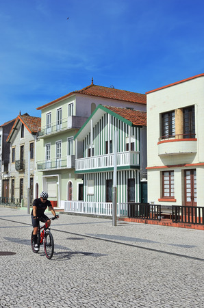 Costa Nova, Portugal - June 09, 2017: Cyclist on the  bicycle in famous resort on the Atlantic coast in Beira Litoral. Popular tourist destination to spend vacation time