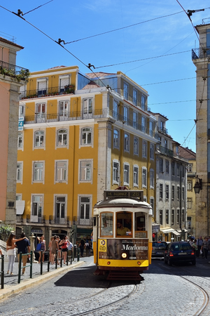 Lisbon, Portugal - June 11, 2017: Vintage tram famous number 28 route on the streets of romantic old Alfama. Rua da Madalena, Lisbon, Portugal
