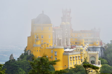 The view of Pena National Palace in Sintra covered with white clouds at beautiful summer mist sunrise, Portugal Stock Photo