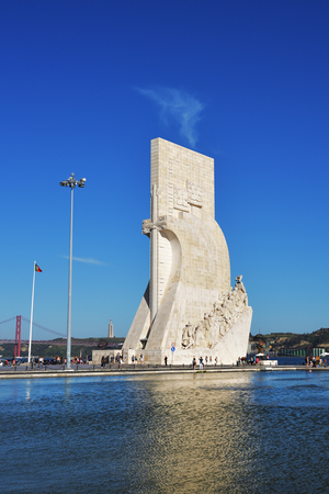 discoverer: LISBON, PORTUGAL - JUNE 11, 2017: Monument to the Discoveries (Padrao dos Descobrimentos) at the Tagus river with view on 25th of April Bridge