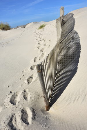 Footsteps near wooden fence on the sand dunes at Costa Nova, a famous beach near Aveiro, Centro, Portugal