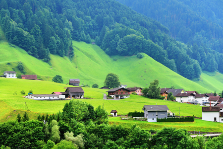 alpen: Altdorf, Switzerland - June 14, 2017: Beautiful view of idyllic mountain scenery in the Alps with traditional chalets and farm in green alpine meadows in Uri canton