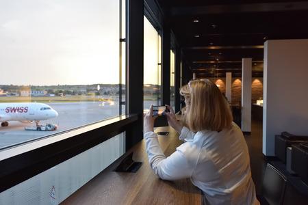 pone: Kloten, Switzerland - May 30, 2017: Zurich airport departure area interior. Woman passenger taking pictures of the plane on the smartphone. Zurich Kloten Airport is the largest international airport of Switzerland