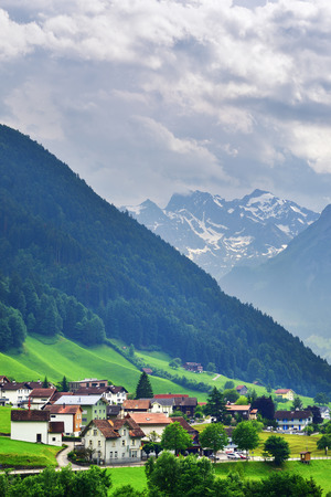 Beautiful view of idyllic mountain scenery in the Alps with traditional chalets in fresh green alpine meadows in Uri canton nearby Altdorf city, Switzerland