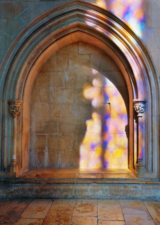 Colored flecks of sunlight from stained glass on the stone wall of the Batalha Santa Maria da Vitoria Dominican abbey, Portugal.  UNESCO World Heritage Site