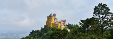 View on the Pena National Palace and surrounding park in Sintra in beautiful summer mist sunrise, Portugal