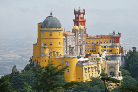 Panoramic view of Pena National Palace in Sintra in a beautiful summer mist sunrise, Portugal. Film like color Stock Photo