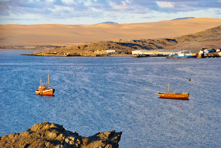 Small fishing boats in bay of Luderitz at sunset. Luderitz is a harbour town lying on one of the least hospitable coasts in Africa