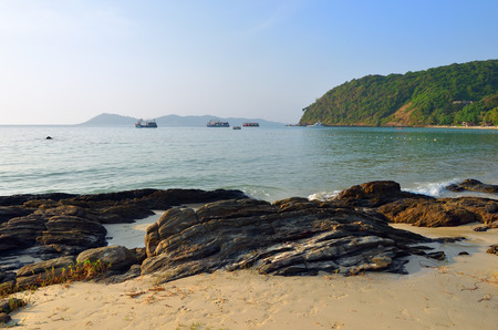 Tropical island of the Koh Samet, stone beach and sea with boats at sunset