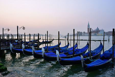 Gondolas moored by Saint Mark square with San Giorgio di Maggiore church in the background at sunrise. Venice, Italy, Europe