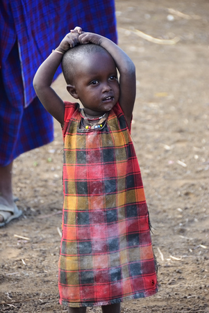 NGORONGORO CONSERVATION AREA, TANZANIA - JAN 24, 2008: Little unidentified tanzanian child from Masai tribe dressed with simple and dirty clothes shown in a village near Ngorongoro