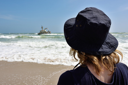 Lonely woman standing on the beach looking at the sinking ship from shipwreck. Atlantic coast in Namibia, also known as Skeleton coast. Africa