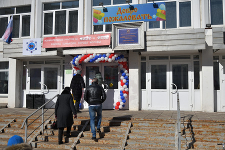 Moscow, Russia - March 18, 2018: The president election in Russia. People going to the entrance of the polling station. The text means