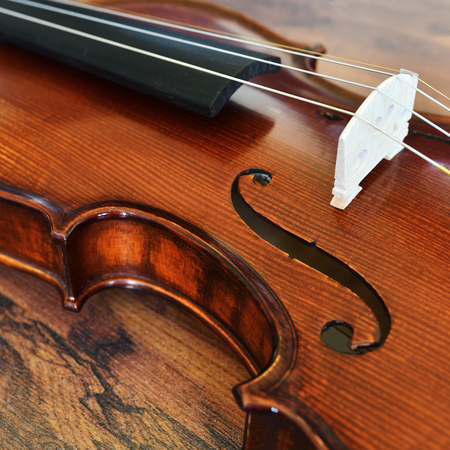 Violin waist detail on rustic wooden background. Shallow depth of field