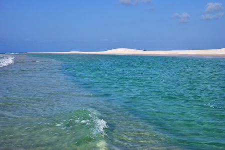 Azure water and white sand dune. A sandy coastline and a colorful lone cliff at the sunset. Qalansiya beach in the lagoon Detwah Socotra island Yemen