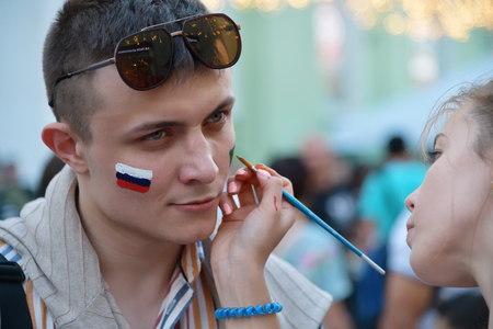 Moscow, Russia - June 23, 2018: The girl draws the symbols of the Russian team on the face of a football fann the Nikolskaya streets in Moscow, FIFA world cup, Mundial 2018 Редакционное