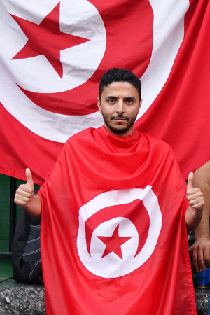Moscow, Russia - June 23, 2018: Tunisian fan with national flag on Nikolskaya street in Moscow. FIFA world cup, Mundial 2018