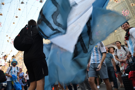 Moscow, Russia - June 23, 2018: Football fans from Argentina and waving national flag on the streets of Moscow. Soccer fans from abroad walking down the Nikolskaya streets in Moscow, FIFA world cup, Mundial 2018 Редакционное