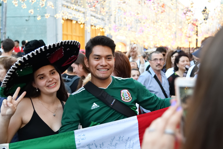 Moscow, Russia - June 23, 2018: Football fans from Mexica with national flag on the Nikolskaya streets in Moscow, FIFA world cup, Mundial 2018 Редакционное
