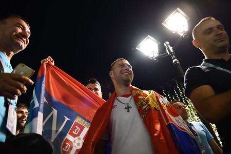 Moscow, Russia - June 26, 2018: Serbian football fans with national flags on the Nikolskaya street in Moscow at night. FIFA world cup, Mundial 2018