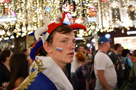 Moscow, Russia - June 26, 2018: Russian football fan on the night streets of Moscow. Soccer fans from abroad walking down the Nikolskaya street in Moscow. FIFA world cup, Mundial 2018
