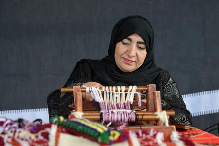 Moscow, Russia - July 14, 2018: A senior arabian woman makes a traditional sadu weaving. Qatar
