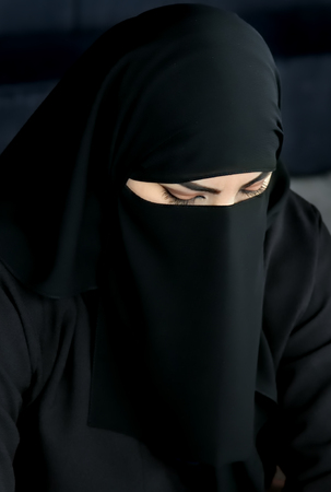 Moscow, Russia - July 14, 2018: Portrait of an arabic young woman from Qatar in traditional islamic cloth niqab against on dark background. Typical clothing of women of the Middle East
