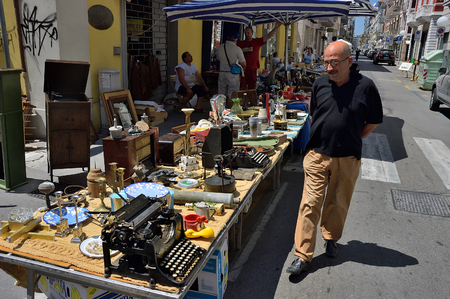 Pescara, Italy - July 2, 2006: A man looking on a goods, arts and etc displayed for sale at Pescara street flea market. This flea market very popular between locals and tourists Redactioneel