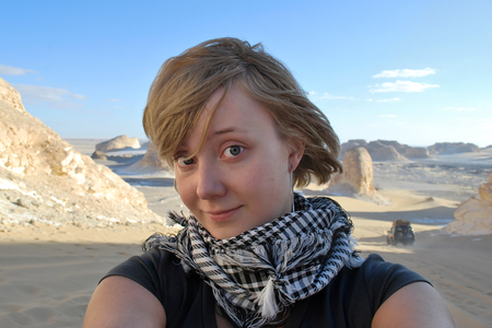 Close-up portrait of the blonde girl-traveler dressed in fishnet pattern keffiyeh or kufiya arabic scarf making selfie in desert. Extreme travel concept