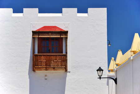 White architecture house fragment in Lanzarote. Traditional building exterior. Wooden spanish balcony and street lights. Playa Blanca, Canary Islands, Spain