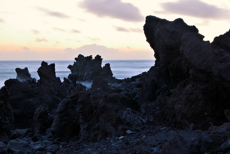 Unusual forms of volcanic cliffs of lava on the rocky shore. Beautiful sunset over the Atlantic Ocean. Los Hervideros, Lanzarote, Canary Islands. Spain