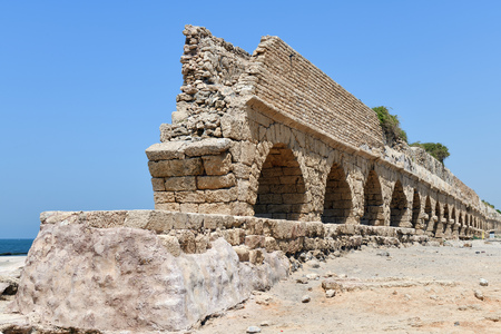 The ruins of the ancient Roman Aqueduct in city of Caesarea Maritima are located by the sea shore of Israel Standard-Bild - 121184637