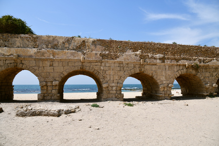 The ruins of the ancient Roman Aqueduct in city of Caesarea Maritima are located by the sea shore of Israel Standard-Bild