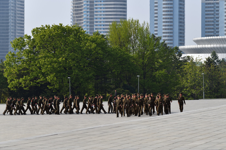 Pyongyang, North Korea - May 1, 2019: A company of soldiers marching along Pyongyang Street against the background of skyscrapers. Mansu hill