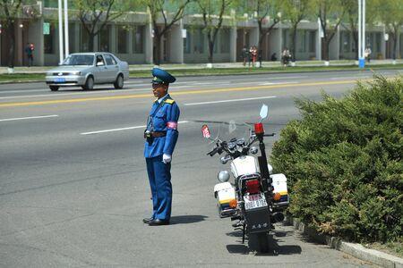 Pyongyang, North Korea - May 1, 2019: Traffic policeman with a motorcycle regulates traffic at an intersection Banco de Imagens - 128464893