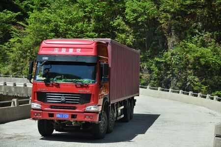North Korea - April 30, 2019: Road in Countryside. The Red Heavy Truck