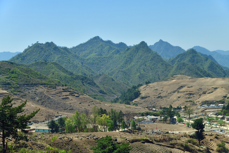 Countryside landscape, North Korea. Cultivated agricultural field? village and mountain at background