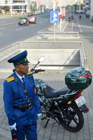 Pyongyang, North Korea - April 29, 2019: Traffic policeman with a motorcycle regulates traffic at an intersection